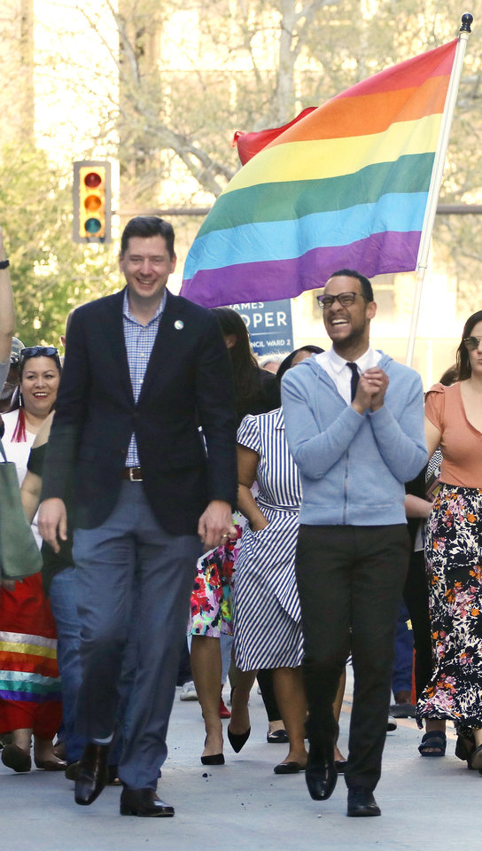Photo - Marchers join Councilman-elect James Cooper, left, and Mayor David Holt in a march from Main and Broadway to City Hall in support of the LGBTQ community, Monday, April 8, 2019.  Photo by Doug Hoke/The Oklahoman