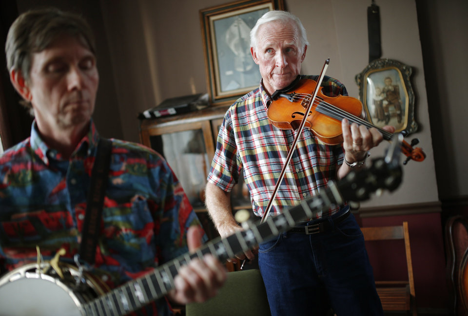 Photo -  Byron Berline, right, and Billy Perry warm up before playing a concert at the music hall upstairs from Berline's Double Stop Fiddle Shop in Guthrie. [Photo by Bryan Terry, The Oklahoman Archives]