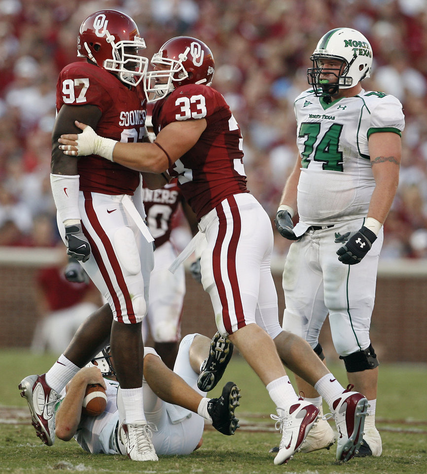 Photo - Oklahoma's Cory Bennett (97) and Auston English (33) celebrate in front of North Texas' Adam Venegas (74) after a sack in the first half during the University of Oklahoma Sooners (OU) college football game against the University of North Texas Mean Green (UNT) at the Gaylord Family - Oklahoma Memorial Stadium, on Saturday, Sept. 1, 2007, in Norman, Okla.
