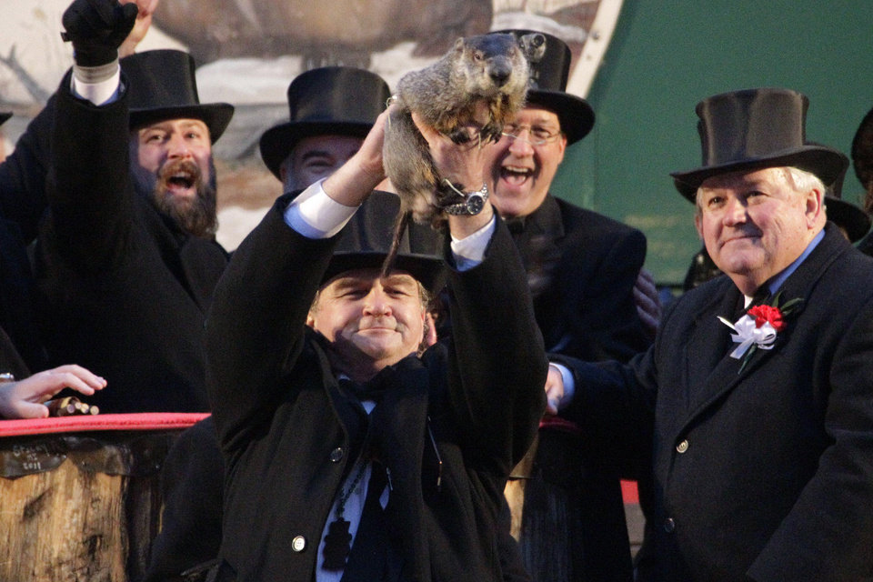 Photo - Groundhog Club handler John Griffiths holds Punxsutawney Phil, the weather prognosticating groundhog, during the 126th celebration of Groundhog Day on Gobbler's Knob in Punxsutawney, Pa. Thursday, Feb. 2, 2012. Phil saw his shadow, forecasting six more weeks of winter weather. (AP Photo/Gene J. Puskar)