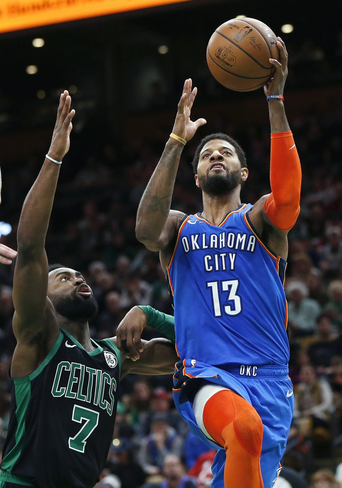 Photo - Oklahoma City Thunder's Paul George (13) shoots in front of Boston Celtics' Jaylen Brown (7) during the second half of an NBA basketball game in Boston, Sunday, Feb. 3, 2019. (AP Photo/Michael Dwyer)