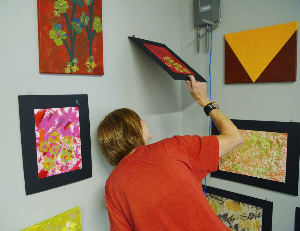 Photo -  Soni Parsons hangs a piece of art by Derek Prophet, an art class regular with the fresh stART program at The Homeless Alliance day shelter in Oklahoma City. Police shot and killed Prophet on May 25. Prophet was a prolific artist who encouraged others and liked to help out at the shelter, said Parsons, volunteer coordinator with the fresh stART program at The Homeless Alliance day shelter. [Photos by Jim Beckel, The Oklahoman]