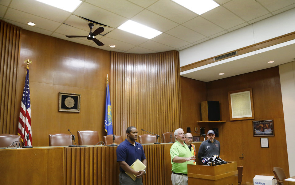 Photo - A fan and a ceiling tile hang precariously above city officials in the council chambers during a briefing with media as City Manager Steve Spears and other department heads provide damage updates to reporters at city hall on Monday, Nov. 7, 2016.  Spears said city hall sustained some damage as a result of Sunday night's 5.0 magnitude earthquake. Sections of the ceiling collapsed in Assistant City Manager Jeremy Frazier's office, leaving insulation and debris on the floor. A large window on the front of the building was broken during the shaking. Photo by Jim Beckel, The Oklahoman