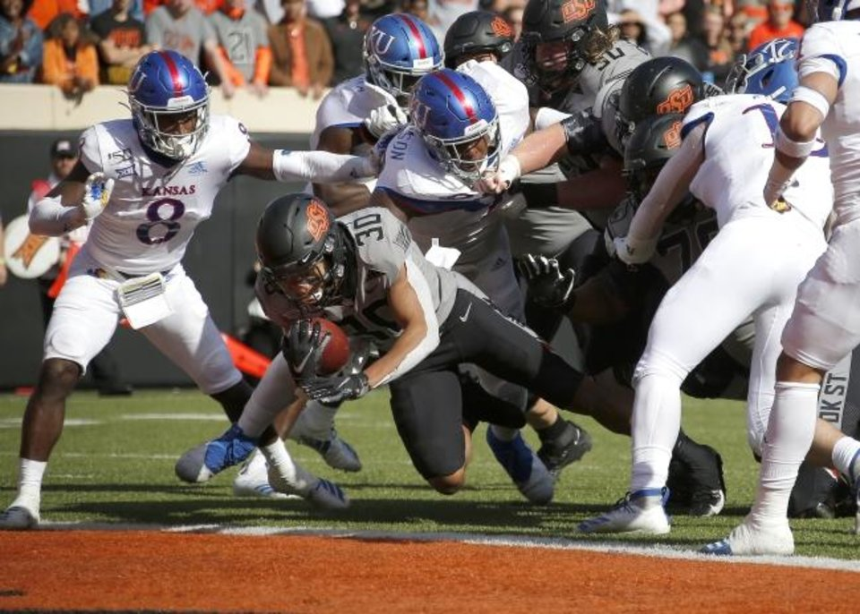 Photo -  Oklahoma State's Chuba Hubbard scores a touchdown against Kansas last week. [Sarah Phipps/The Oklahoman]
