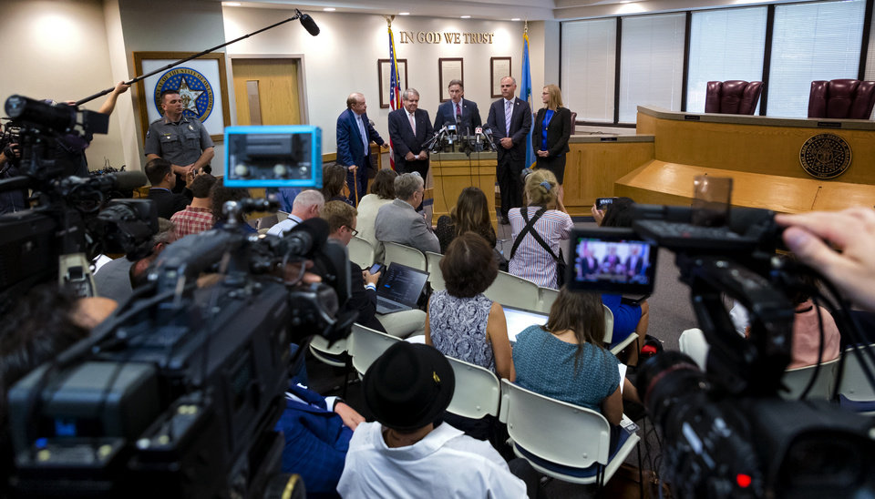 Photo - State's attorneys and Terri White, Oklahoma Department of Mental Health and Substance Abuse Services Commissioner led by Attorney General Mike Hunter, center, take to the media after Judge Thad Balkman delivered his decision in the opioid trial at the Cleveland County Courthouse in Norman, Okla. on Monday, Aug. 26, 2019. Judge Balkman ruled in favor of the State of Oklahoma, that Johnson and Johnson pay $572 million to a plan to abate the opioid crisis. The proceeding were the first public trial to emerge from roughly 2,000 U.S. lawsuits aimed at holding drug companies accountable for the nationÕs opioid crisis.  [Chris Landsberger/Pool]