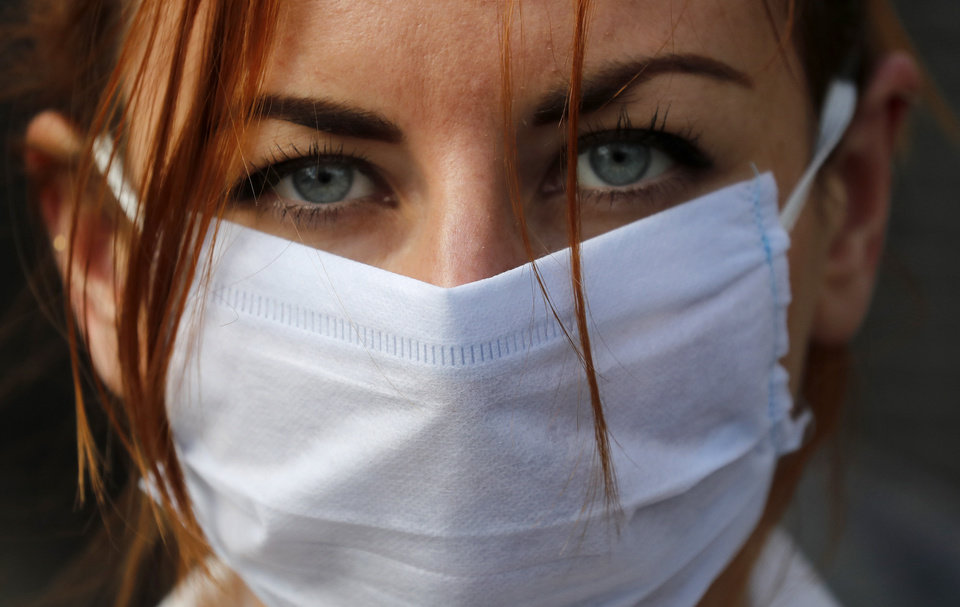 Photo -  An member of the group 'Pause the System' wears a face mask as she protests in front of the entrance to Downing Street in London, Friday, March 20, 2020. For most people, the new coronavirus causes only mild or moderate symptoms, such as fever and cough. For some, especially older adults and people with existing health problems, it can cause more severe illness, including pneumonia. (AP Photo/Frank Augstein)