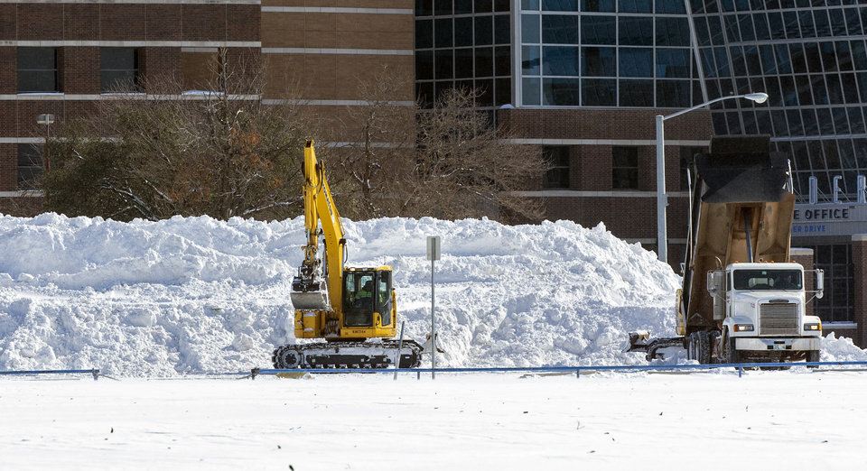 Photo - Crews work to unload snow removed from city streets in the parking lot west of the Chesapeake Energy Arena in Oklahoma City, Okla. on Monday, Feb. 15, 2021.  [Chris Landsberger/The Oklahoman]