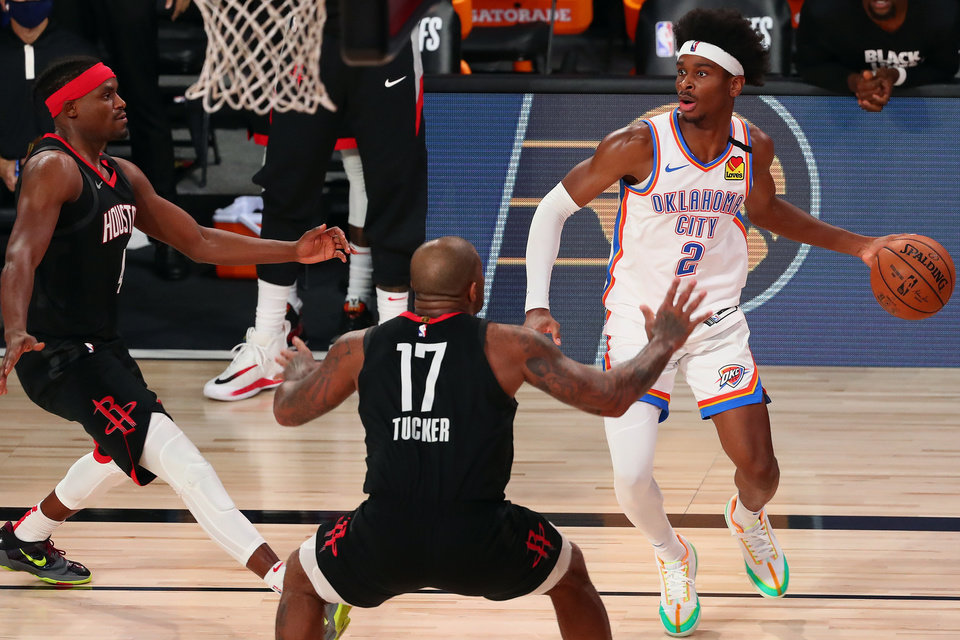 Photo - Aug 24, 2020; Lake Buena Vista, Florida, USA; Oklahoma City Thunder guard Shai Gilgeous-Alexander (2) controls the ball against Houston Rockets forward Danuel House Jr. (left) and forward P.J. Tucker (17) during the second half in game four of the first round of the 2020 NBA Playoffs at AdventHealth Arena. Mandatory Credit: Kim Klement-USA TODAY Sports
