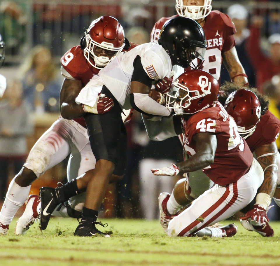 Photo - Oklahoma's Kenneth Murray (9) and Mark Jackson Jr. (42) stop Army's Kelvin Hopkins Jr. (8) during a college football game in which the University of Oklahoma Sooners (OU) defeated the Army Black Knights 28-21 at Gaylord Family-Oklahoma Memorial Stadium in Norman, Okla., on Saturday, Sept. 22, 2018. Photo by Steve Sisney, The Oklahoman