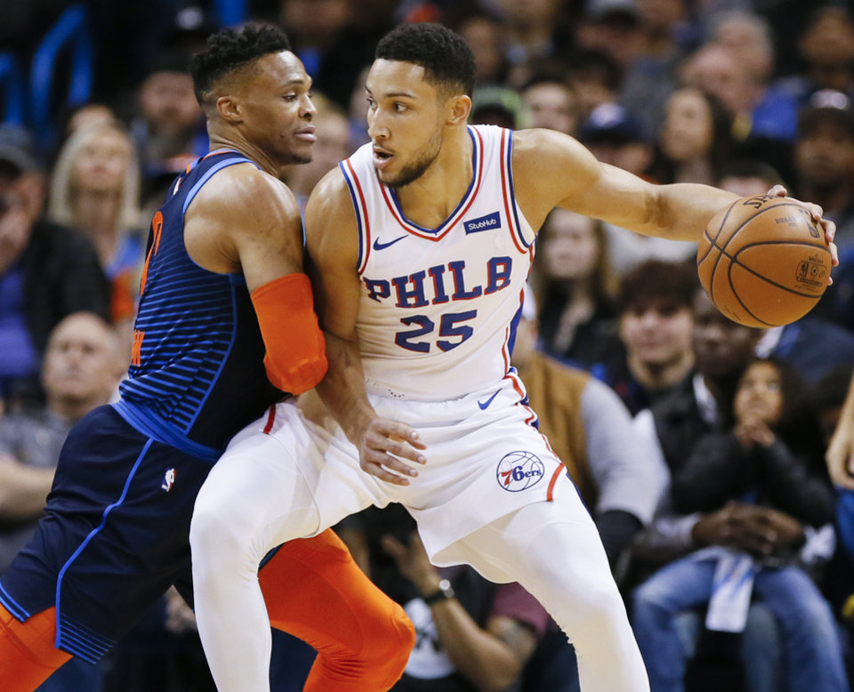 Photo - Oklahoma City's Russell Westbrook (0) defends Philadelphia's Ben Simmons (25) in the first quarter during an NBA basketball game between the Philadelphia 76ers and the Oklahoma City Thunder at Chesapeake Energy Arena in Oklahoma City, Thursday, Feb. 28, 2019. Photo by Nate Billings, The Oklahoman