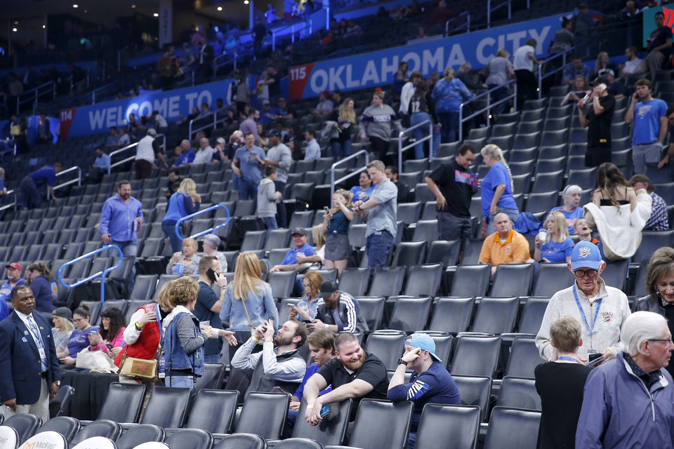 Photo - Oklahoma City Thunder fans leave after an NBA basketball game between the Oklahoma City Thunder and the Utah Jazz was postponed at Chesapeake Energy Arena in Oklahoma City, Wednesday, March 11, 2020. [Bryan Terry/The Oklahoman]
