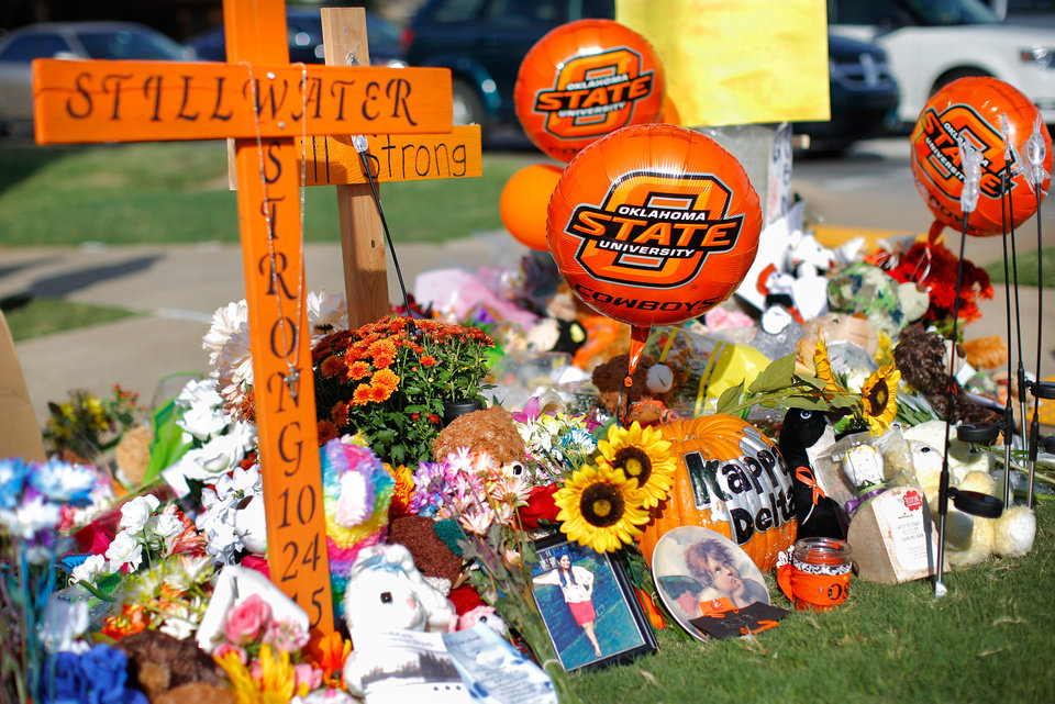 Photo -  Remembrances and tributes filled the corner of Hall of Fame Avenue and Main Street in Stillwater for days after last year's fatal crash at the Oklahoma State University homecoming parade. [Photo by Jim Beckel, The Oklahoman Archives]
