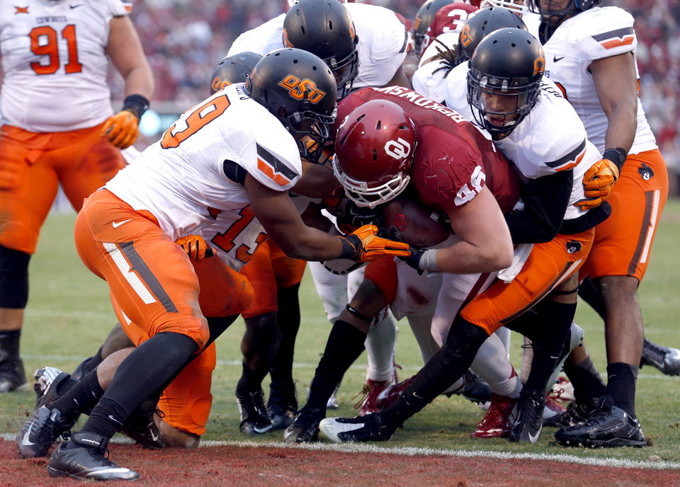 Photo - Oklahoma's Aaron Ripkowski (48) scores a touchdown as he is tackled by a host of Oklahoma State defenders during the Bedlam college football game between the University of Oklahoma Sooners (OU) and the Oklahoma State Cowboys (OSU) at Gaylord Family-Oklahoma Memorial Stadium in Norman, Okla., Saturday, Dec. 6, 2014. Photo by Sarah Phipps, The Oklahoman