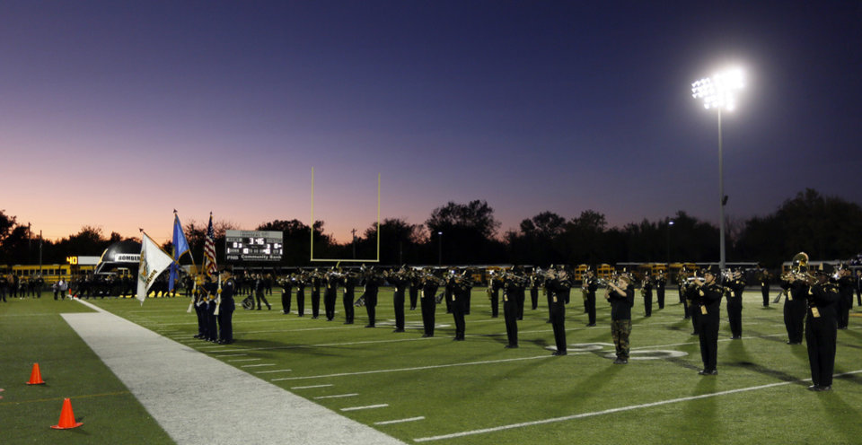 Photo - The Midwest City band plays the national anthem as the sun sets before a high school football game between Midwest City and Choctaw at Rose Field in Midwest City, Okla., Friday, Nov. 1, 2019. [Nate Billings/The Oklahoman]