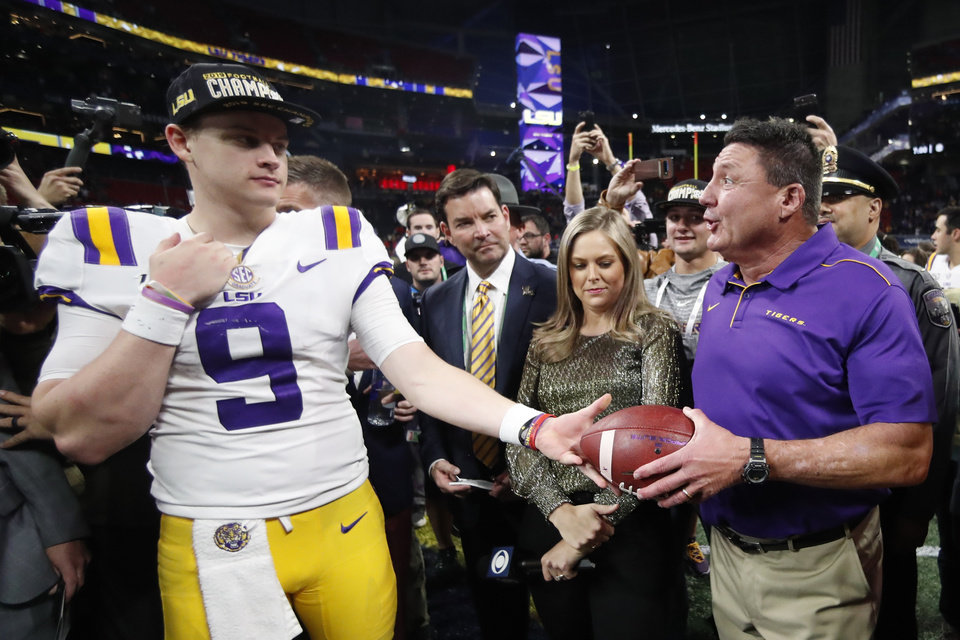 Photo - LSU quarterback Joe Burrow and LSU head coach Ed Orgeron celebrate after the Southeastern Conference championship NCAA college football game against Georgia, Saturday, Dec. 7, 2019, in Atlanta. LSU won 37-10. (AP Photo/John Bazemore)
