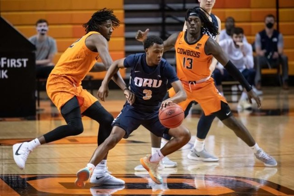 Photo -  ORU guard Max Abmas, center, is defended by Oklahoma State Cowboys forward Kalib Boone, left, and guard Isaac Likekele on Tuesday. [Rob Ferguson/USA TODAY Sports]