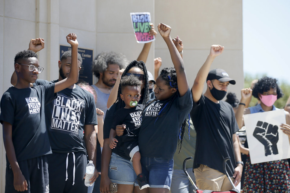 Photo - Protestors raise their hands for eight minutes and 46 seconds during a protest in front of the Edmond Police Department in Edmond, Okla., Saturday, June 6, 2020. The protest was organized in response to the shooting death of Isaiah Lewis by Edmond Police last year and the death of George Floyd in Minneapolis. [Bryan Terry/The Oklahoman]