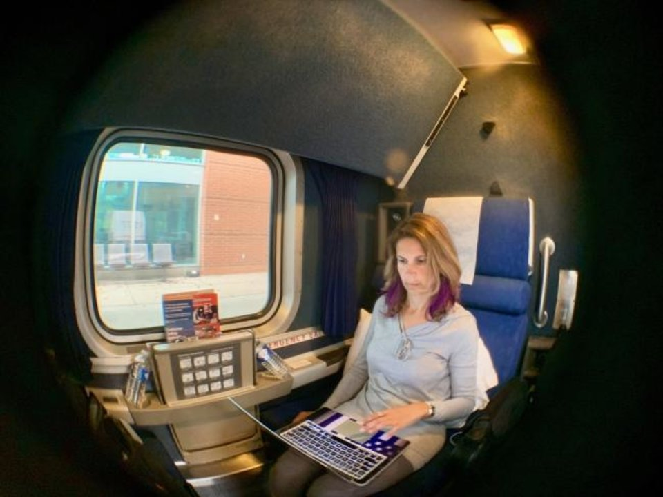 Photo -  Sylvia Longmire works on a laptop in her roomette on the train. [Sylvia Longmire]