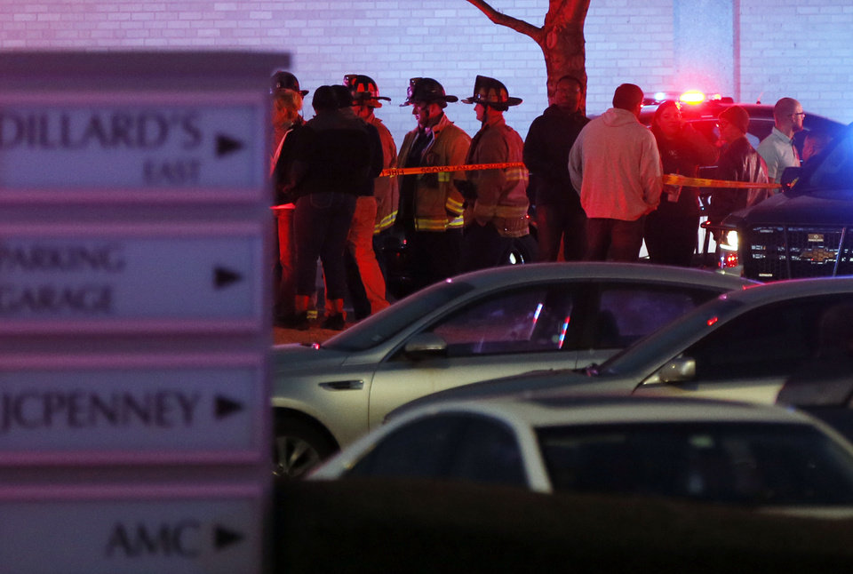 Photo - People stand on the south side of Penn Square Mall as the sun sets after a shooting at the mall in Oklahoma City, Thursday, Dec. 19, 2019. [Nate Billings/The Oklahoman]