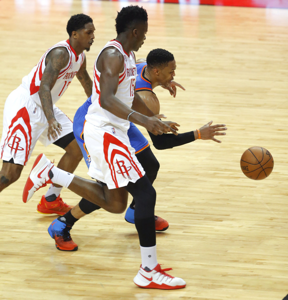 Photo - Oklahoma City's Russell Westbrook (0) goes between Houston's Lou Williams (12) and Clint Capela (15) during Game 2 in the first round of the NBA basketball playoffs between the Oklahoma City Thunder and the Houston Rockets at the Toyota Center in Houston, Texas,  Wednesday, April 19, 2017.  Photo by Sarah Phipps, The Oklahoman