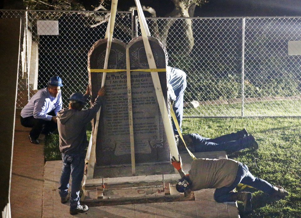 Photo - FILE - In this Monday, Oct. 5, 2015 file photo, workers remove the Ten Commandments monument from its base on the grounds of the state Capitol in Oklahoma City. Oklahoma's lawmakers want voters to decide four issues in next month's election, including one that would let them erect a Ten Commandments monument at the state Capitol and others enshrining executions, farmers' rights and liquor sales in the state's constitution. (AP Photo/Sue Ogrocki, File)