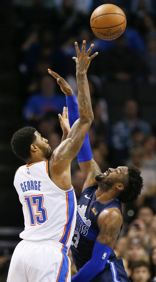 Photo - Oklahoma City's Paul George (13) shoots over Dallas' Wesley Matthews (23) during an NBA basketball game between the Oklahoma City Thunder and Dallas Mavericks at Chesapeake Energy Arena in Oklahoma City, Monday, Dec. 31, 2018. Oklahoma City won 122-102. Photo by Nate Billings, The Oklahoman