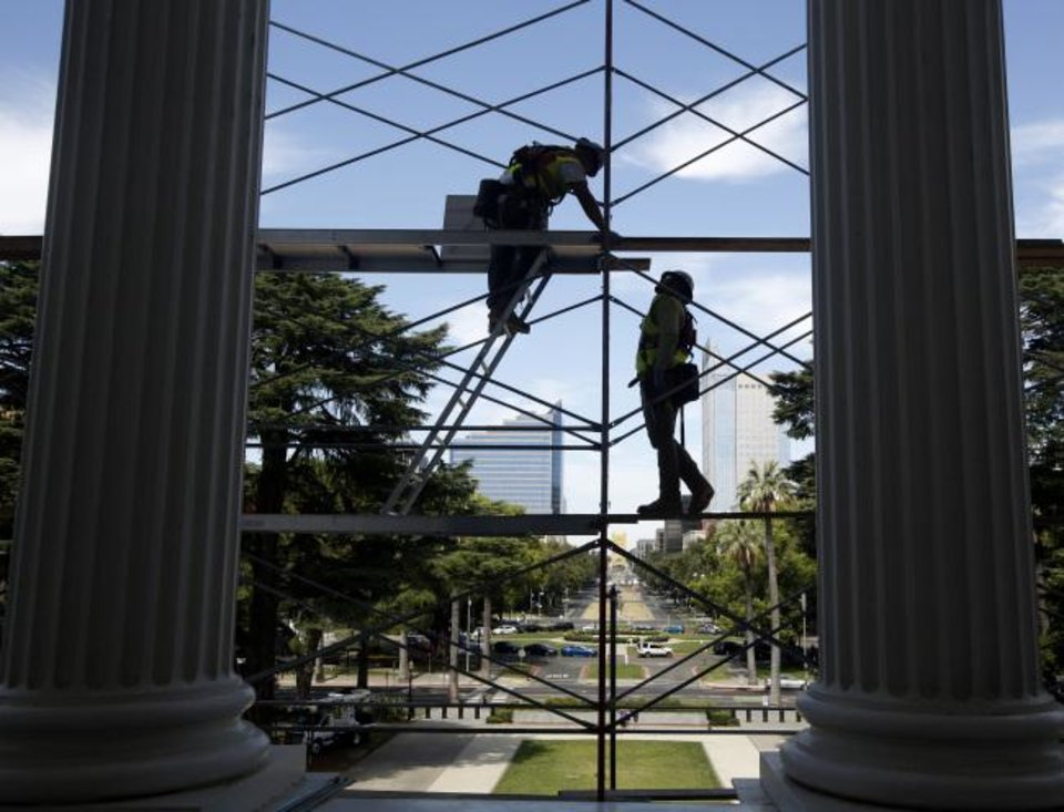 Photo -  Workers assemble scaffolding on the west side of the state Capitol in preparation for a routine maintenance project, in Sacramento, Calif. [AP PHOTO]