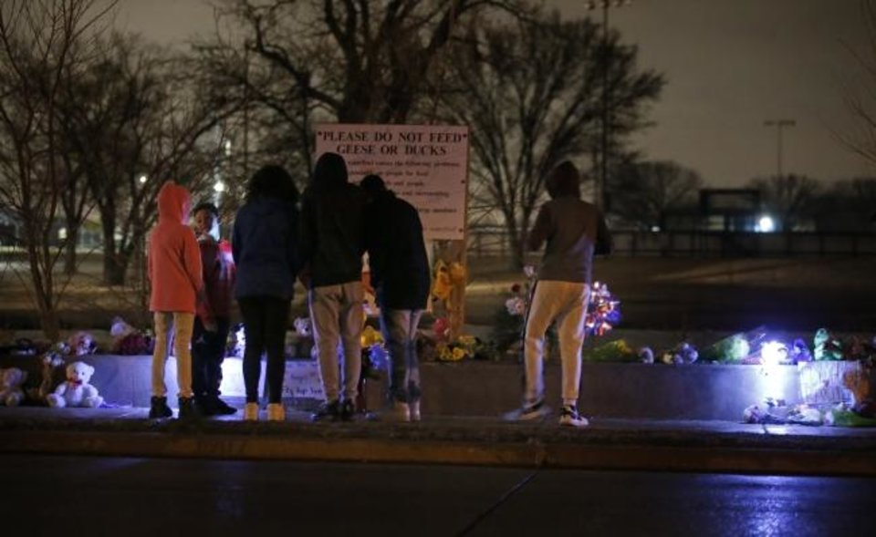Photo -  People gather Tuesday around make-shift memorials at the site of a hit and run incident in Moore near Moore High School. [Sarah Phipps/The Oklahoman]