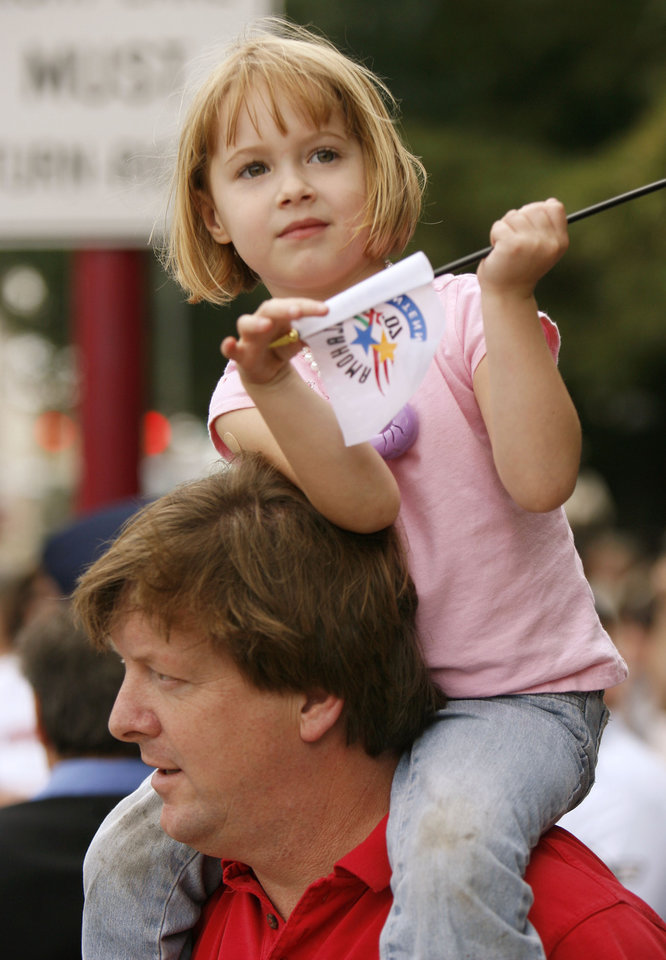 Photo - Lily Arnold, 4, sits on the shoulders of her dad Shawn during the Oklahoma Centennial Parade in downtown Oklahoma City, Okla., Sunday, October 14, 2007. Photo by Paul Hellstern / The Oklahoman.