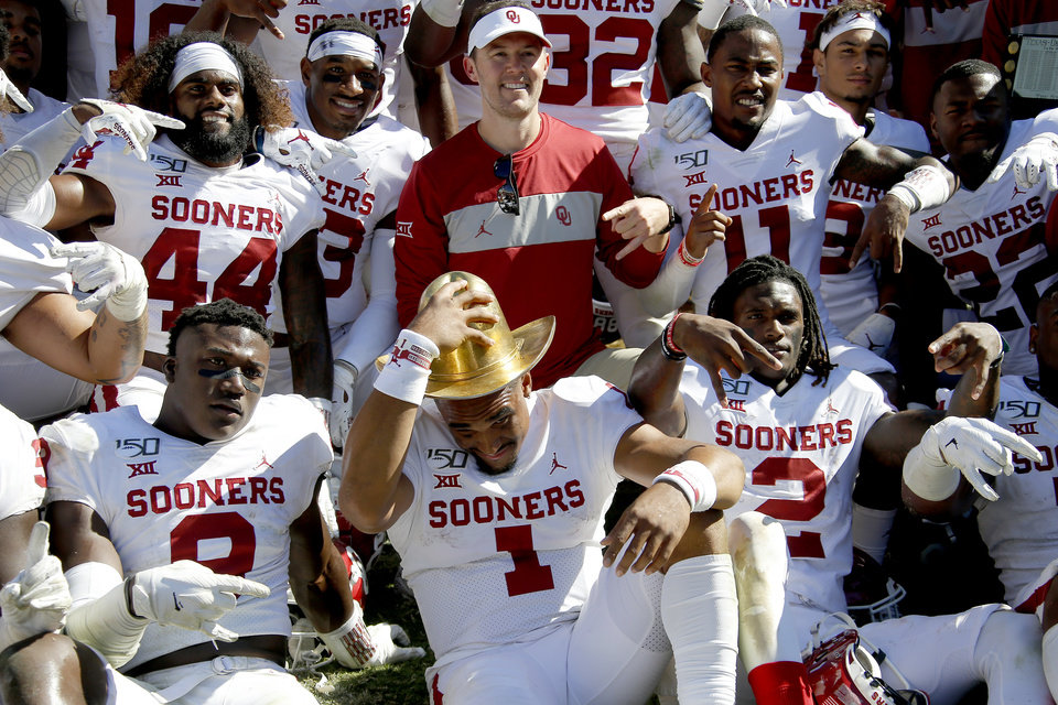 Photo - Oklahoma coach Lincoln Riley poses for a photo behind Kenneth Murray (9), Jalen Hurts (1) and CeeDee Lamb (2) after the Red River Showdown college football game between the University of Oklahoma Sooners (OU) and the Texas Longhorns (UT) at Cotton Bowl Stadium in Dallas, Saturday, Oct. 12, 2019. Oklahoma won 34-27. [Bryan Terry/The Oklahoman]