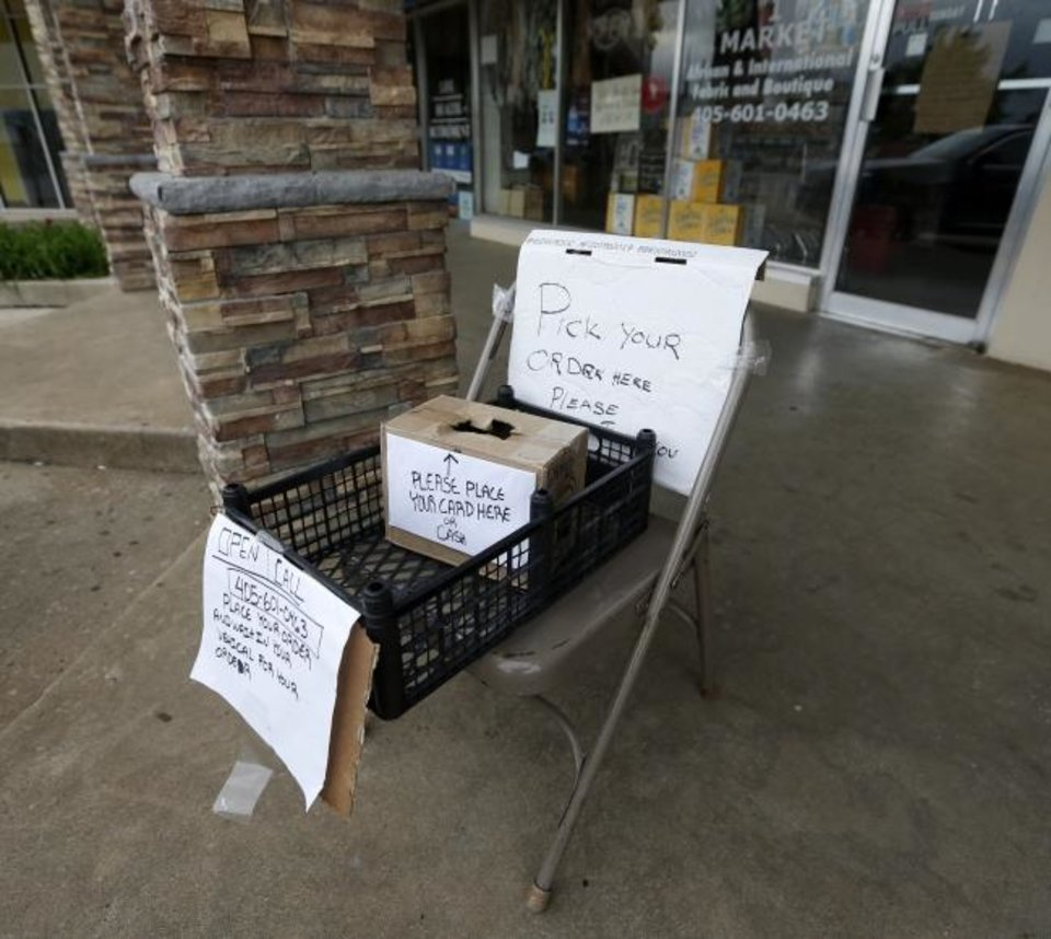 Photo -  A basket and chair are used to provide distance between employees and customers picking up items Thursday from Makola #1 Market in the Jade Asian Plaza in the Asian District in Oklahoma City. [Nate Billings/The Oklahoman]