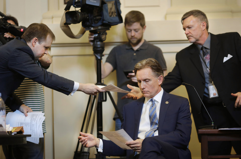 Photo - Mike Hunter reads documents introduced as evidence by the attorney for Gentner Drummond as he is questioned by the attorney, Garry Gaskins, left, who hands the same paperwork to a clerk for the state election board. Oklahoma Attorney General Mike Hunter can remain on the ballot after the Oklahoma Election Board voted 3-0 on Monday, April 23, 2018, to deny a challenge to his candidacy on residency grounds. Hunter, a Republican, testified he always kept Oklahoma as his permanent home even though he lived in Virginia for years while working in Washington, D.C. for two trade organizations.