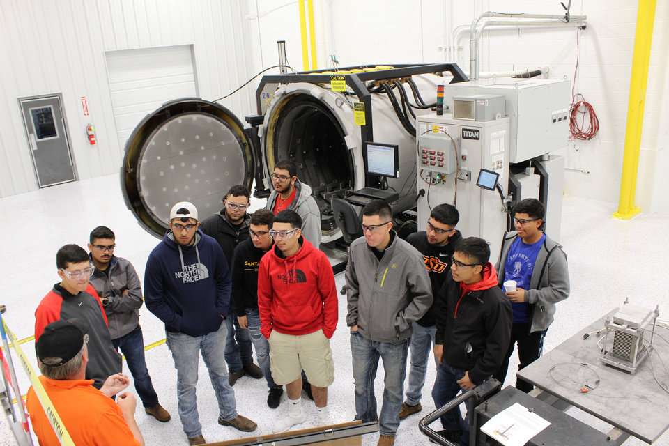 Photo -  Bryan Brasel explains high temperature vacuum brazing to a group of students from Santa Fe South High School at WCC Aerobraze OKC, 4700 SE 59, earlier this year on Manufacturing Day. The state-of-the art, high-temperature vacuum brazing furnace, installed in April 2017, produces parts made from stainless steel or inconel, a nickel alloy, and used in F-16 and F-15 aircraft. A second furnace is scheduled for delivery in November. Both furnaces will be housed in this newly remodeled clean room. [PHOTO PROVIDED BY WCC AEROBRAZE OKC]