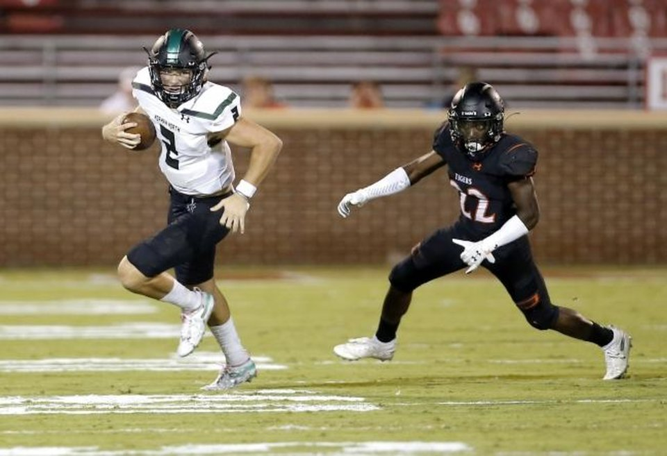 Photo -  Norman North's Jackson Remualdo (2) rushes away from Norman's Jackson Caldwell during a game last year. The two schools will face off in the playoffs on Friday. [Sarah Phipps/The Oklahoman]