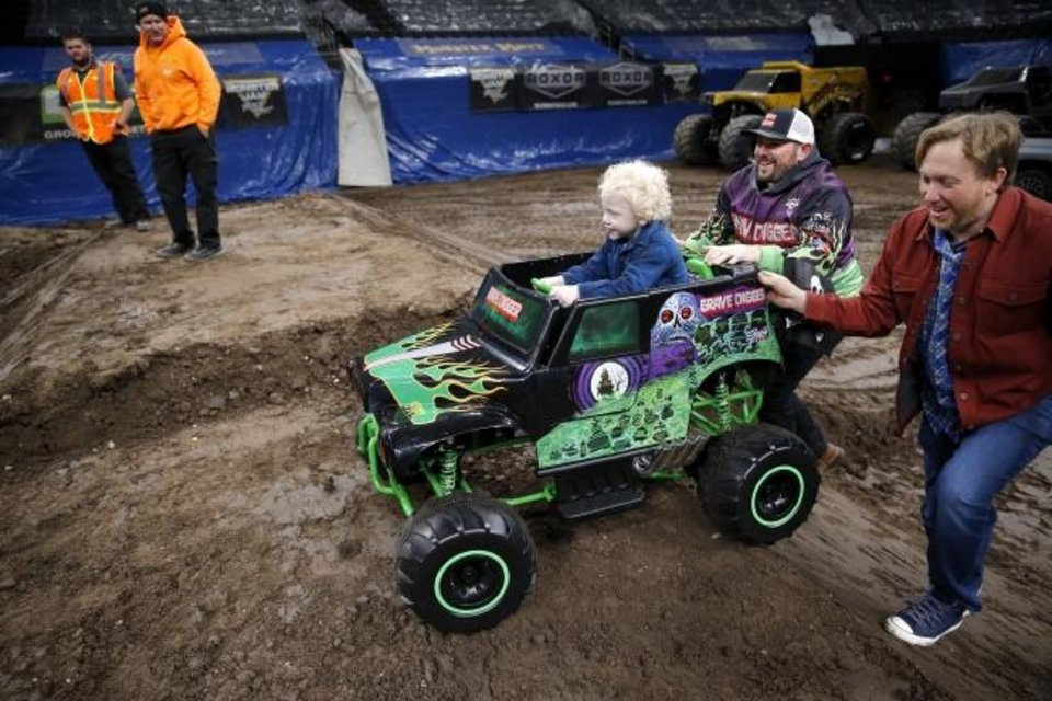 Photo -  Monster Jam driver Grave Digger, Brandon Vinson, and Ryan Ammons help Ryker Ammons, 4, of Yukon, Okla., up a hill on the track at Chesapeake Energy Arena in Oklahoma City, Friday, Feb. 14, 2020.  [Sarah Phipps/The Oklahoman]