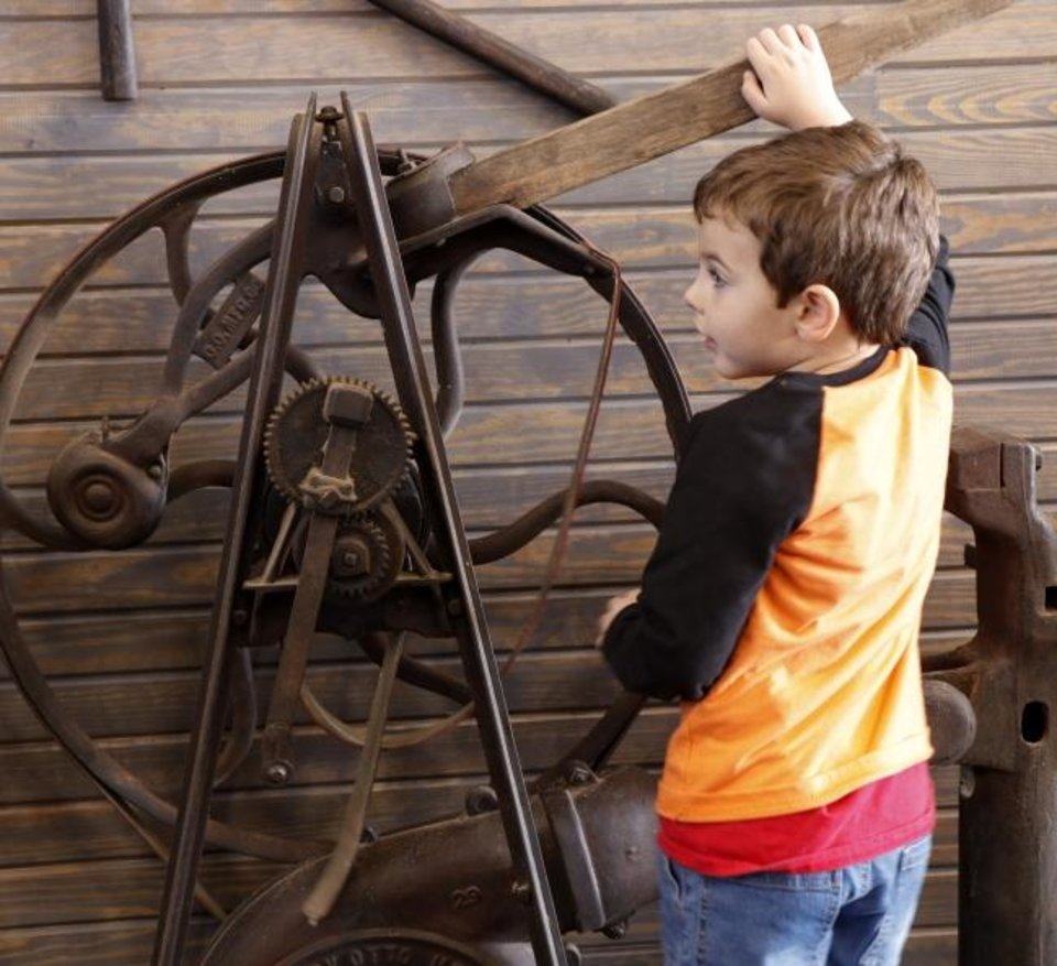 Photo -  Matteo Hengel, 4, Choctaw, tries out a machine at the opening of the Museum of Horseshoeing during the Stockyards Stampede on Saturday. [Doug Hoke/The Oklahoman]