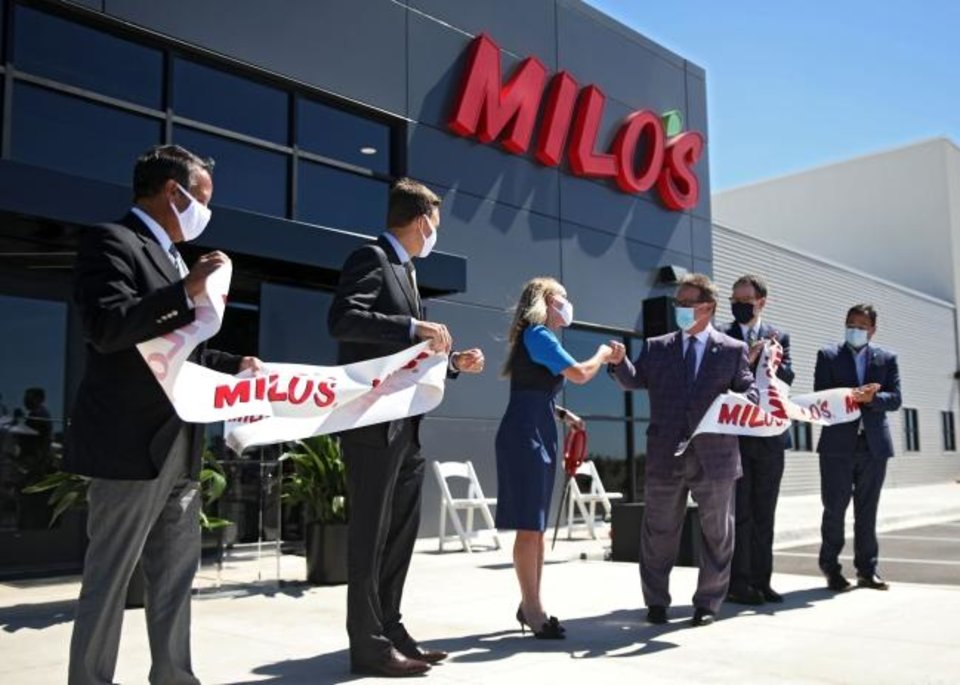 Photo -  Milo's Tea Company CEO Tricia Wallwork fist bumps Mike Neal of the Tulsa Regional Chamber after cutting a ribbon at a ceremony marking the opening of Milo Tea Company's production facility in Owasso. The company chose Owasso over Oklahoma City after finding no suitable sites. [MIKE SIMONS/TULSA WORLD]