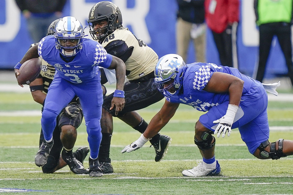 Photo -  Kentucky quarterback and former Del City star Terry Wilson (3) runs with the ball against Vanderbilt on Saturday in Lexington, Ky. [AP Photo/Bryan Woolston]