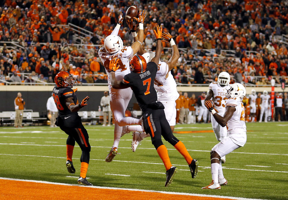 Photo - Texas Dylan Haines (44) grabs a mary in front of Oklahoma State's James Washington (28) and Brandon Sheperd (7) at the end of the first half during the college football game between the Oklahoma State University Cowboys (OSU) the University of Texas Longhorns (UT) at Boone Pickens Staduim in Stillwater, Okla. on Saturday, Nov. 15, 2014.  Photo by Sarah Phipps, The Oklahoman
