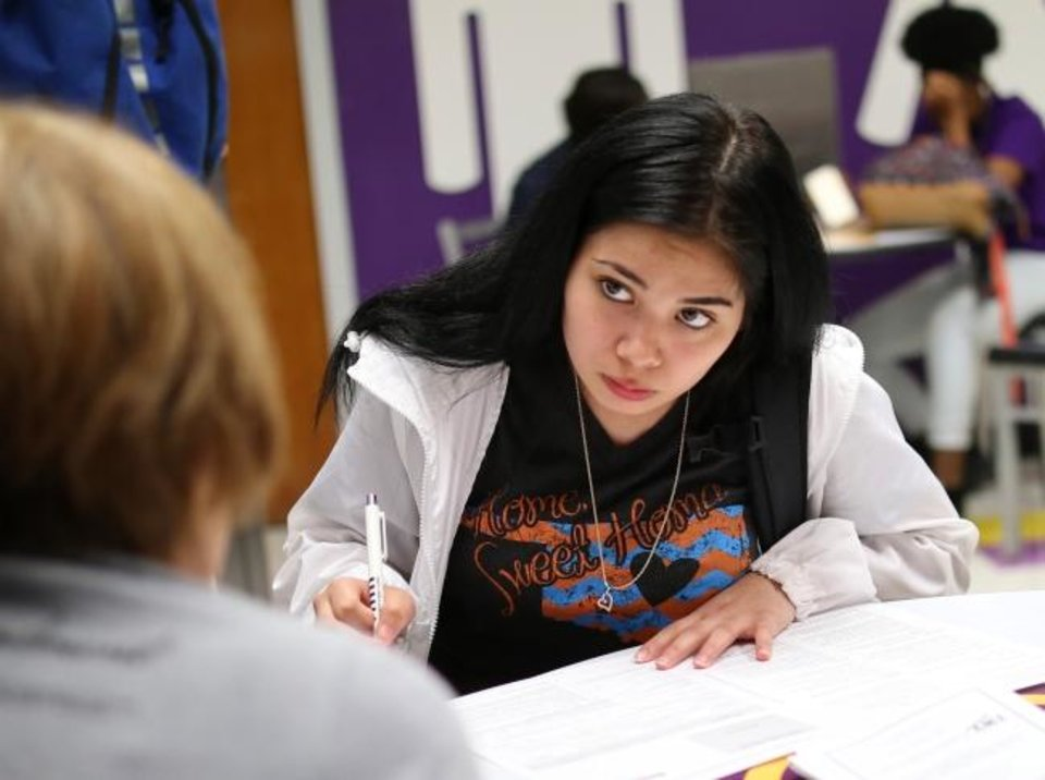 Photo -  Diamond Alvarez, 18, fills out a voter registration form Wednesday. [Doug Hoke/The Oklahoman]