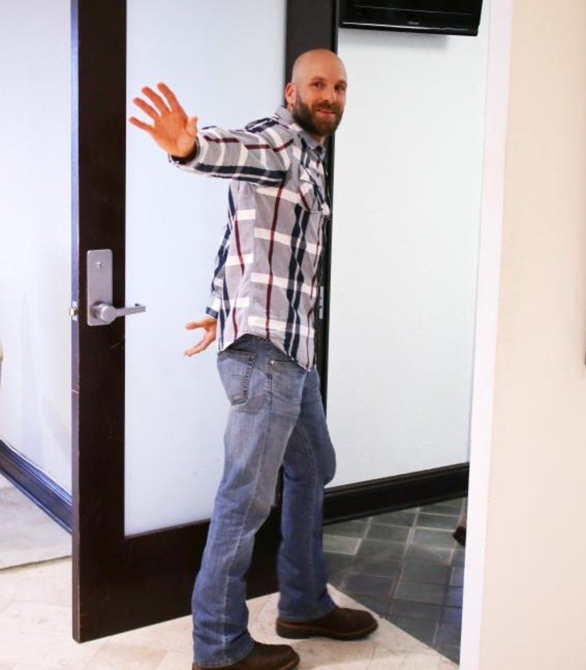 Photo -  Michael Behenna waves as he enters an office after a news conference on Wednesday.