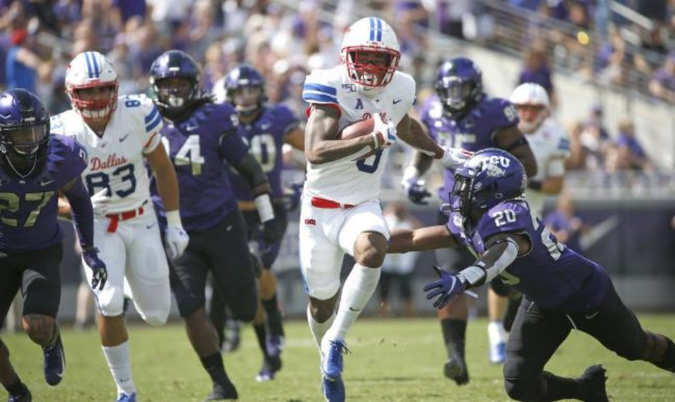 Photo -  SMU wide receiver Reggie Roberson Jr. (8) runs past TCU safety La'Kendrick Van Zandt (20) after catching a pass for a first down during the Mustangs' 41-38 win over the Horned Frogs on Saturday in Fort Worth, Texas. [AP Photo/Ron Jenkins]