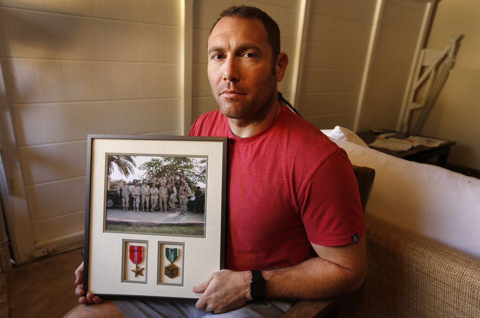 Photo - Robert D'Andrea, a retired Army major and Iraq war veteran, holds a frame with a photo of his team on his first deployment to Iraq on Friday, Oct. 21, 2016 in his home in Los Angeles.  Nearly 10,000 California National Guard soldiers have been ordered to repay huge enlistment bonuses a decade after signing up to serve in Iraq and Afghanistan.  The Pentagon demanded the money back after audits revealed overpayments by the California Guard under pressure to fill ranks and hit enlistment goals. If soldiers refuse, they could face interest charges, wage garnishments and tax liens,  D'Andrea said he was told to repay his $20,000 because auditors could not find a copy of the contract he says he signed. (Al Seib/Los Angeles Times via AP)