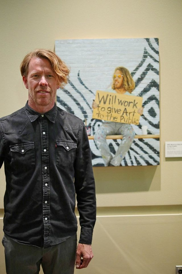 Photo - Oklahoma artist Rick Sinnett stands in front of his portrait by Mike Wimmer in Wimmer's