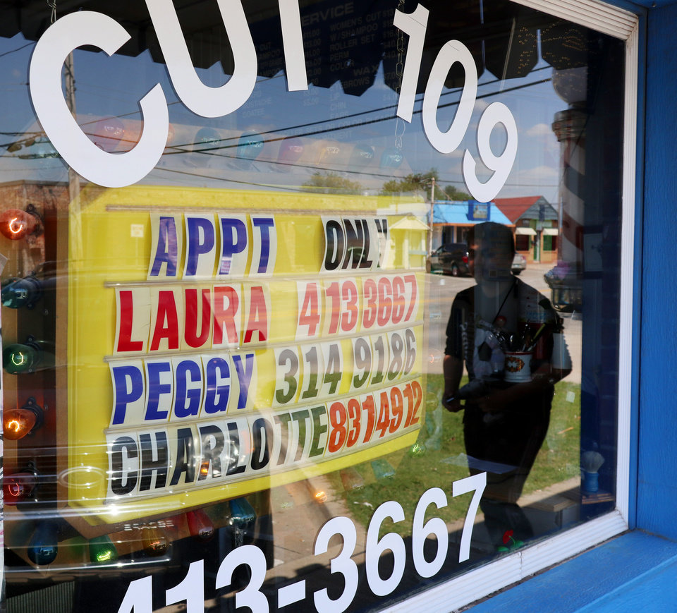 Photo - Sign in the window at Cut 109 lets people know they can schedule appointments in Moore, Monday, April 27, 2020.  [Doug Hoke/The Oklahoman]