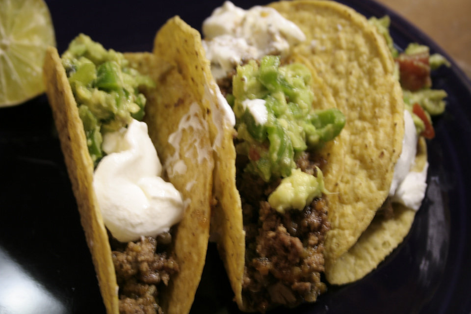 Photo -  Green chile tacos with guacamole, sour cream and a ribbon of honey.