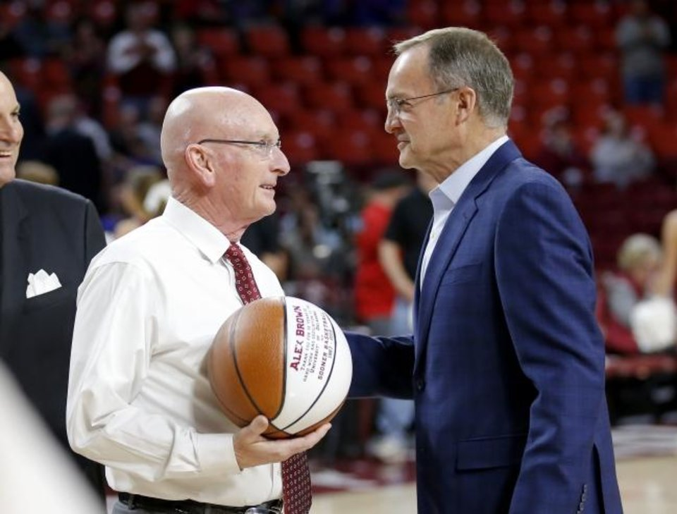 Photo -  OU men's basketball athletic trainer Alex Brown, left, is congratulated by coach Lon Kruger before a March 5 game against Kansas at Lloyd Noble Center. Brown is retiring after this season, his 32nd with the Sooners. [Sarah Phipps/The Oklahoman]
