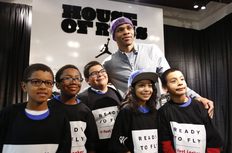 Photo - Russell Westbrook, top, poses for a photo with Josiah Vinson, 9, Anthony Pikes, 12, Jacob Bustos, 11, Mariah Stigger, 9, and Joey Bustos, 10, from the Oklahoma County boys and Girls Clubs at the House of Hoops in Penn Square Mall, Wednesday, December 10, 2014. Photo by David McDaniel