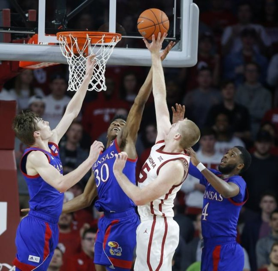 Photo -  Oklahoma's Brady Manek puts up a shot between Kansas' Christian Braun, left, Ochai Agbaji, center, and Isaiah Moss, right, during Tuesday night's Big 12 basketball  game at Lloyd Noble Center. [Bryan Terry/The Oklahoman]