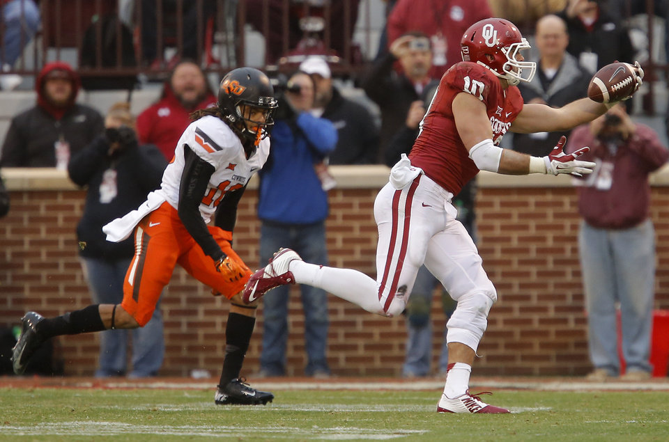 Photo - Oklahoma's Blake Bell (10) makes a catch in front of Oklahoma State's Ramon Richards (18) during a Bedlam college football game between the University of Oklahoma Sooners (OU) and the Oklahoma State Cowboys (OSU) at Gaylord Family-Oklahoma Memorial Stadium in Norman, Okla., Saturday, Dec. 6, 2014. Photo by Bryan Terry, The Oklahoman